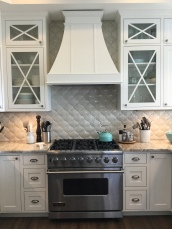 Closer image of stove and cabinets with backsplash