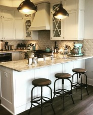 Custom cabinets and Anne Sacks tile backsplash with industrial lights.