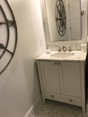 Pretty bathroom with marble counters, tilting mirror and nautical compass on the wall.